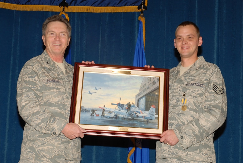McGHEE TYSON AIR NATIONAL GUARD BASE, Tenn. -- Staff Sgt. Adam B. Thornton, right, an enlisted professional military education instructor, receives a heritage painting from Col. Richard B. Howard, commander, upon his departure from assignment at The I.G. Brown Air National Guard Training and Education Center here, Dec. 18, 2009.  (U.S. Air Force photograph by Master Sgt. Mavi Smith/Released)
