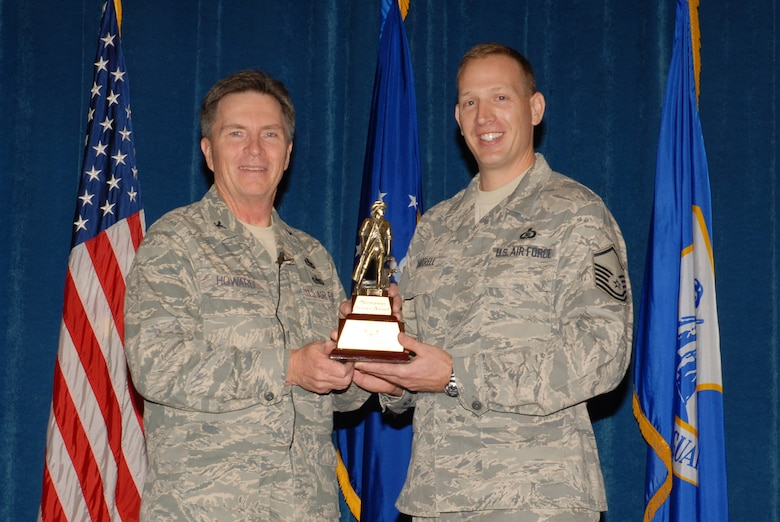 McGHEE TYSON AIR NATIONAL GUARD BASE, Tenn. -- Master Sgt. Herbert J. Harrell, right, an enlisted professional military education instructor, receives the meritorious service award from Col. Richard B. Howard, commander, upon his departure from assignment at The I.G. Brown Air National Guard Training and Education Center here, Dec. 18, 2009. (U.S. Air Force photograph by Master Sgt. Mavi Smith/Released)
