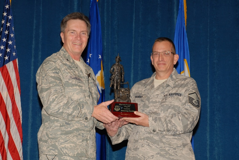 McGHEE TYSON AIR NATIONAL GUARD BASE, Tenn. -- Master Sgt. Andrew D. Traugot, right, an instructional systems analyst for the enlisted professional military education branch, receives the honorary faculty award from Col. Richard B. Howard, commander, upon his departure from assignment at The I.G. Brown Air National Guard Training and Education Center here, Dec. 18, 2009.  (U.S. Air Force photograph by Master Sgt. Mavi Smith/Released)
