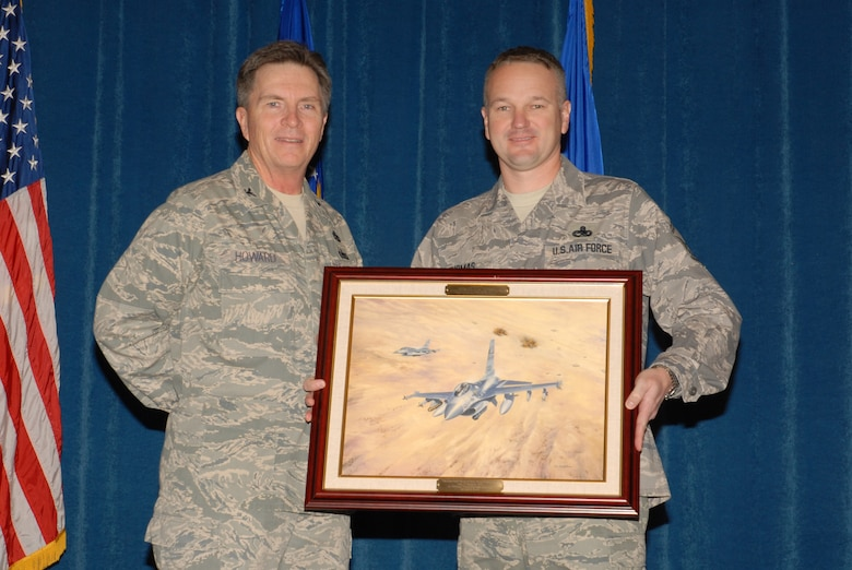 McGHEE TYSON AIR NATIONAL GUARD BASE, Tenn. -- Senior Master Sgt. Kevin Thomas, right, the director of resources for enlisted professional military education, receives a heritage painting from Col. Richard B. Howard, commander, upon his departure from assignment at The I.G. Brown Air National Guard Training and Education Center here, Dec. 18, 2009.  (U.S. Air Force photograph by Master Sgt. Mavi Smith/Released)