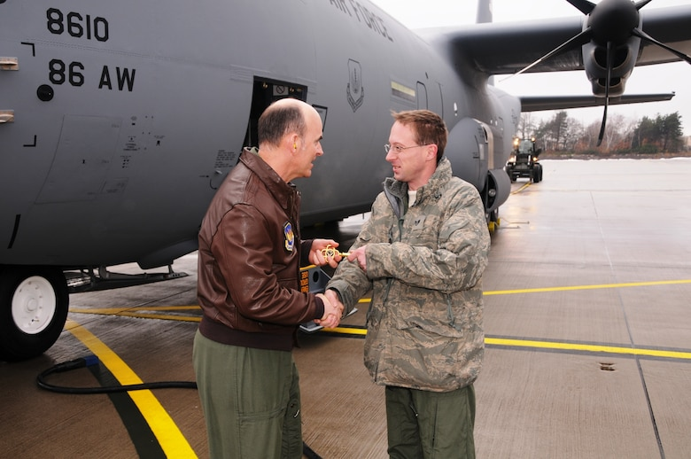 RAMSTEIN AIR BASE, Germany -- 17th Air Force Vice Commander Brig. Gen. Michael Callan hands the ceremonial key to a new C-130J Super Hercules aircraft to 86th Aircraft Maintenance Squadron crew chief Staff Sgt. Jason Keithley after landing the aircraft here Dec. 23. The J-model, one of two aircraft delivered to the 37th Airlift Squadron on the day, gives the unit a total of 10 J-models received. General Callan was latest in a series of Ramstein senior leaders selected to fly the new aircraft back from the Lockheed-Martin plant in Marietta, Ga. (U.S. Air Force photo by Master Sgt. Jim Fisher)