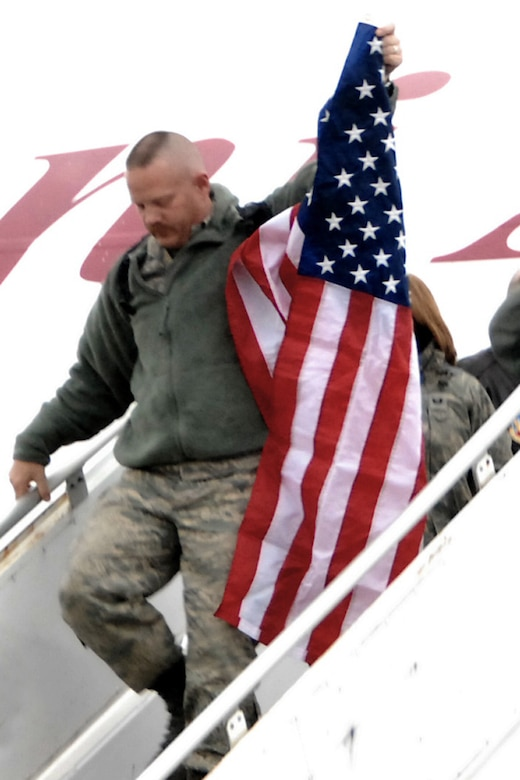 Master Sgt. Ted Davis, fulfilling a time honored tradition at the 132nd Fighter Wing, Des Moines, Iowa by carrying the American flag as he is the first to exit the aircraft of returning deplorers. Master Sgt Davis along with 270 members of the 132nd Fighter Wing returned December 24 to the Iowa Air National Guard Base located at the Des Moines International Airport, from Joint Base Balad, Iraq after filling an aviation package Aerospace Expeditionary Force rotation. (U.S. Air Force/Senior Master Sgt. Tim Day)(Released)