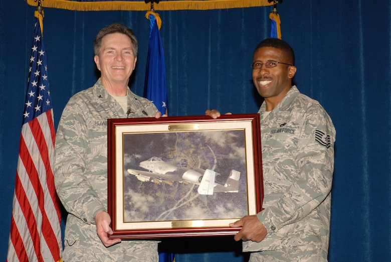 McGHEE TYSON AIR NATIONAL GUARD BASE, Tenn. -- Tech. Sgt. Tyrone E. Melton, right, an enlisted professional military education instructor, receives a heritage painting from Col. Richard B. Howard, commander, upon his departure from assignment at The I.G. Brown Air National Guard Training and Education Center here, Dec. 18, 2009.  (U.S. Air Force photograph by Master Sgt. Mavi Smith/Released)