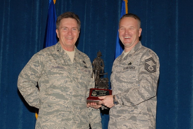 McGHEE TYSON AIR NATIONAL GUARD BASE, Tenn. -- Senior Master Sgt. Kevin Thomas, right, the director of resources for enlisted professional military education, receives the honorary faculty award from Col. Richard B. Howard, commander, upon his departure from assignment at The I.G. Brown Air National Guard Training and Education Center here, Dec. 18, 2009.  (U.S. Air Force photograph by Master Sgt. Mavi Smith/Released)