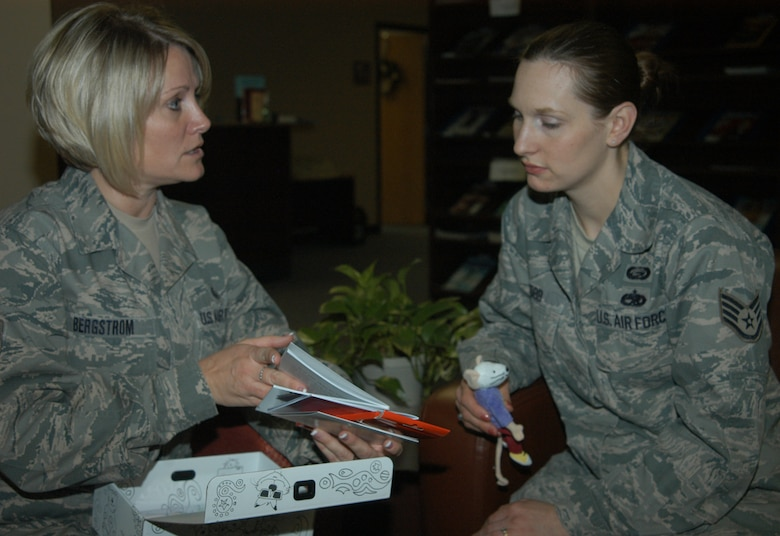 """OFFUTT AIR FORCE BASE, Neb. -- Master Sgt. Stephanie R. Bergstrom (left), superintendent of the Airman and Family Readiness Center for the 55th Force Support Squadron, explains to Staff Sgt. Jessica A. Cobb (right), 55th FSS, how the contents of the """"grief box"""" are meant to be utilized at the AFRC here Dec. 30. Along with her many responsibilities at Offutt's AFRC, Sergeant Bergstrom volunteers with the YWCA, Offutt's sexual assault prevention and response program, and teaches about 12 cardio pulmonary resuscitation classes every year. U.S. Air Force Photo by Staff Sgt. James M. Hodgman"""