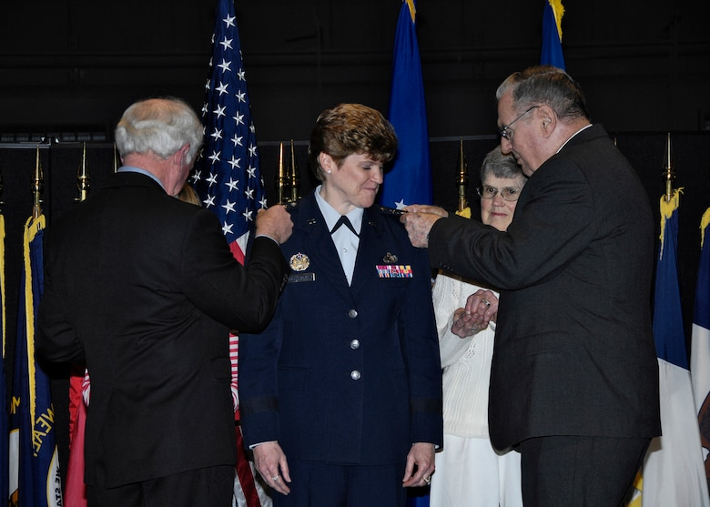 Lt. Gen. Janet C. Wolfenbarger's gets a little help from her family, who helped pin on her three-star rank during a promotion ceremony Dec. 30 at the National Museum of the United States Air Force.  This official ceremony followed the Dec. 4 confirmation by the U. S. Senate of the generals promotion and appointment.  (U.S. Air Force Photo/Mike Libecap)