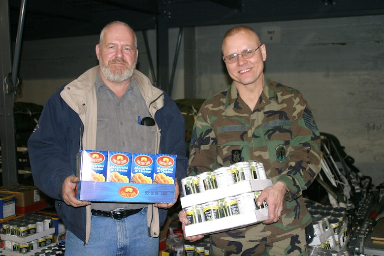 NIAGARA FALLS AIR RESERVE STATION, N.Y. -- For the fourth year in a row, Tech. Sgt. Phil Tillinghast (right) has collected thousands of non-perishable foods for donation to needy families near Niagara Falls ARS at year's end. A cargo processing technician for the 30th Aerial Port Squadron here, Sgt. Tillinghast's 'Christmas Cargo' covered much of the the floor of the squadron building during the unit's annual holiday party Dec. 6, 2008. His long-time friend and civilian coworker Mr. Ronald Shaw (left) helped make it happen for the last two years.  (U.S. Air Force Photo by Mr. Mike Harvey)