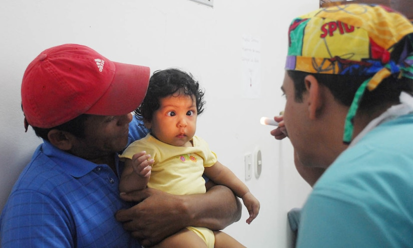 Choluteca, Honduras - Dr. (Maj.) Frank Valentín, a pediatric ophthalmologist from Brooks Army Medical Center, Texas, checks 7-month-old Dilcia Milagro Espinal's eyes before performing surgery to correct her crossed eyes Jan. 28.  Dr. Valentín was in Honduras as part of a 14-person surgical ophthalmology team performing a Medical Readiness and Training Exercise here Jan. 8-30.  (US Air Force photo/Tech. Sgt. Rebecca Danét)