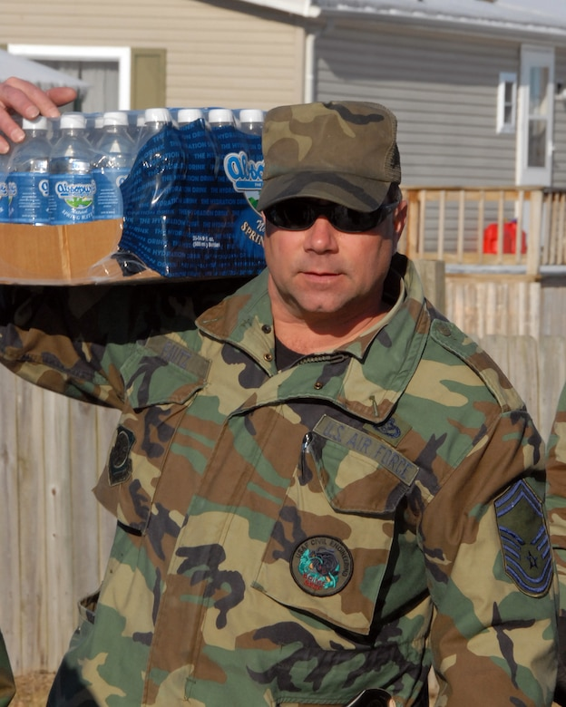 Senior Master Sgt. Marty Fautz of the Kentucky Air National Guard based in Louisville, KY carries bottled water from his truck to the McDaniels Fire Department staging area in McDaniels, KY. during ice storm relief efforts.  (Photo by Tech. Sgt. Dennis Flora / KyANG)