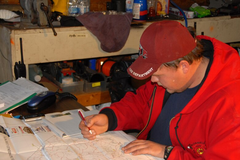 A member of the McDaniels Fire Department plots locations on a map of the area during ice storm relief efforts in McDaniels, KY.  (Photo by Tech. Sgt. Dennis Flora / KyANG)