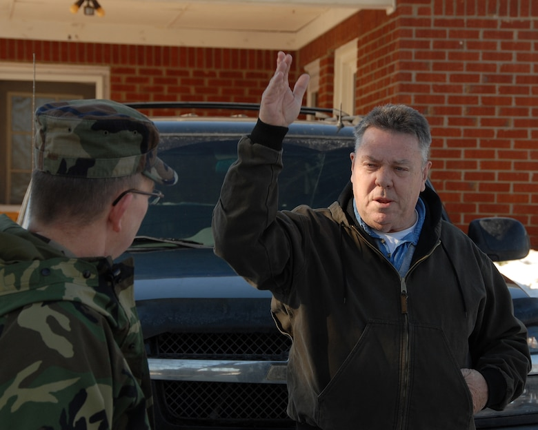 """A McDaniels, KY., resident explains  his situation to a Kentucky Air Guardsman during a door-to-door """"Wellness Check"""" of residents in the area during ice storm relief efforts.  (Photo by Tech. Sgt. Dennis Flora / KyANG)"""