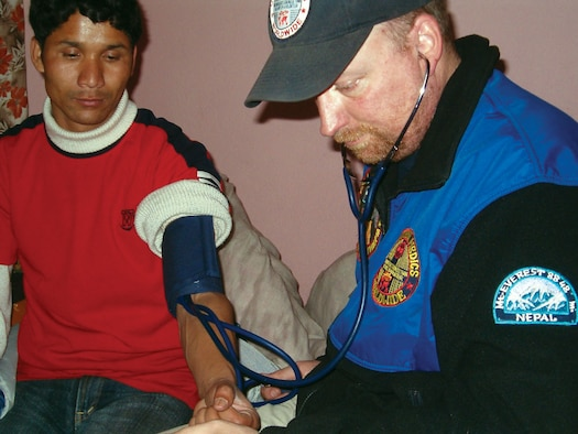 Chris Hamel gives a check up to Mani, director of the orphan children's home in Katmandu, Nepal in March 2008.  When not providing free medical care to citizens of other countries as a member of Volunteer Medics, he is Tech. Sgt. Chris Hamel, a Reservist with 446th Aeromedical Staging Squadron. (Courtesy photo/Gerald Flint)