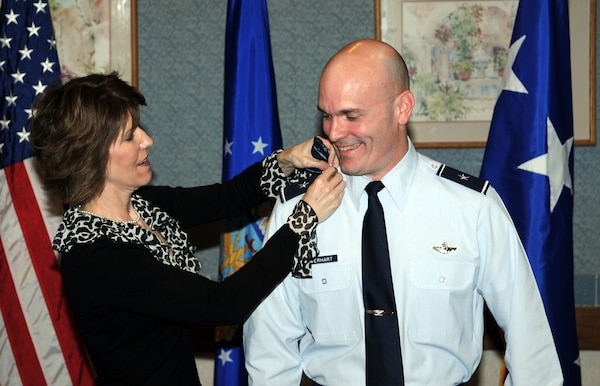 Michelle Everhart, wife of Brig. Gen. Carlton Everhart II, Air Education and Training Command Intelligence and Air, Space and Information Operations for Flying Training deputy director, places new rank on her husbands shoulder boards during his promotion ceremony Jan. 31. (U.S. Air Force photo by Don Lindsey)