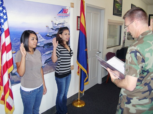 New 162nd Fighter Wing recruits, Vanessa Ferreira and Marie Ann Camara, are sworn in by Lt. Col. Michael Knutson at the base recruiting office. Both Airmen are non-prior service recruits. The recruiting office aims to ensure that at least 30 percent of all recruits are non-prior service. (Air National Guard photo by Senior Master Sgt. (ret.) Ira Zarin)