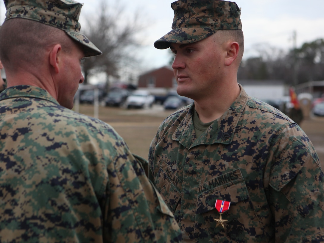 """Lieutenant Colonel Daniel A. Schmitt, the battalion commander for 3rd Battalion, 6th Marine Regiment, 2nd Marine Division, presents the Bronze Star with combat distinguishing device to Sgt. Marcus B. Holan, Feb. 3, 2010 aboard Marine Corps Base Camp Lejeune.  """"It was about the Marines out there,"""" said Holan.  """"Without the supporting arms we wouldn't have made it.  We were just doing what we had to do."""""""