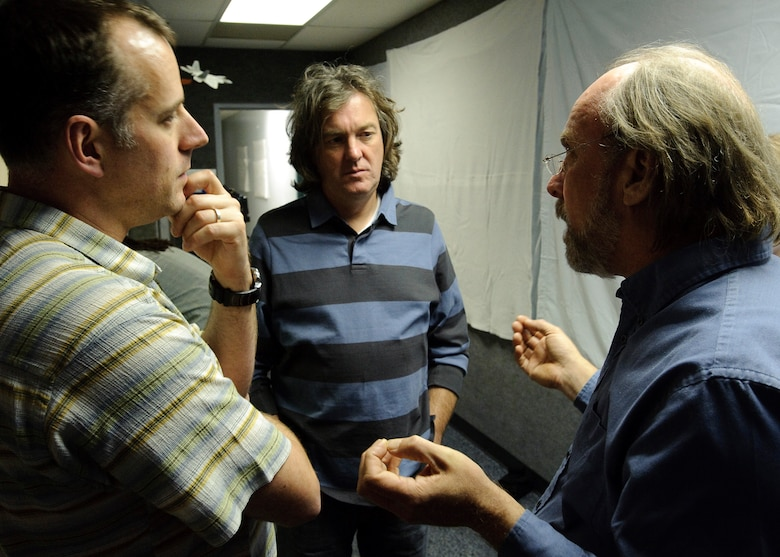 Wayne Isdahl (right) with the Air Force Research Laboratory Centrifuge discusses the mission profile of the Apollo 11 lunar mission during take-off with James May (center), BBC Presenter and Paul King (left), BBC Producer, during production of a documentary by BBC, James May on the Moon which commemorates the 40th anniversary of the Apollo 11 mission, the first to put a man on the Moon. May was spun to several Gs in the AFRL Centrifuge at Brooks City-Base, TX.  His experience allowed  him to be more familiar with the experiences of Apollo 11 Astronauts Neil Armstrong, Michael Collins, and Edwin E. Aldrin, Jr., during the initial phase of launch which entered orbit of the Earth 12 minutes after takeoff. 