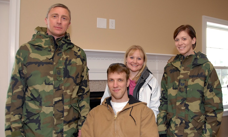 Master Sgt. Kevin Sandberg and Tech. Sgt. Jamie Eastlick,115th Fighter Wing, stand with injured Army veteran Staff Sgt. Charles Isaacson and his wife, Brenda, following a key presentation, inside a newly built Homes for Our Troops home. More than 10 Airmen from the 115 FW contributed to the home, located in Sun Prairie, during a three-day build brigade. The home features many of the special accomodations that Sergeant Isaacson needs to accomodate his injuries from the War on Terror. (U.S. Air Force Photo by Master Sgt. Dan Richardson)