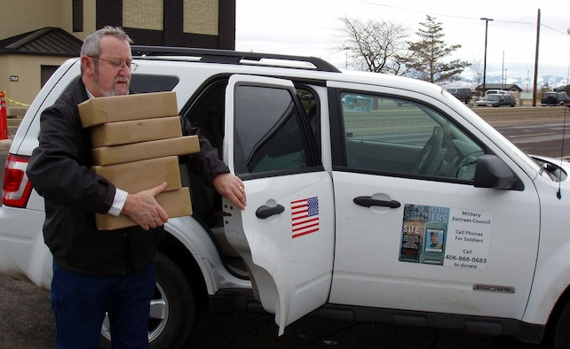 Denis Miller carries packages of old cell phones into the Malmstrom post office Feb. 2. The packages will be sent to a recycling center in Michigan and $5 for each one will be donated to the Cell Phones for Soldiers program on behalf of the Montana Retiree's Council. (U.S. Air Force courtesy photo/Gloria Miller)