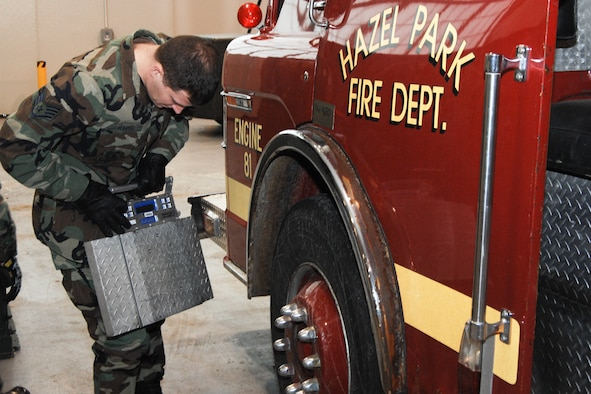 Staff Sgt. Theodore J. Marsh, 171st Aerial Port Flight, conducted a wheel scale weight inspection before the fire truck was allowed to be cleared for transportation to the Dominican Rebublic.