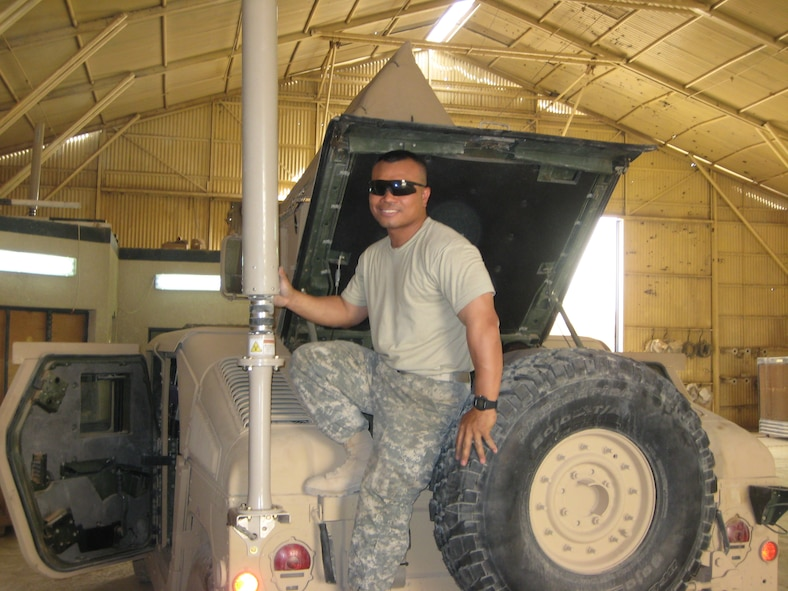 Maj. Joemar Rodrigo, instructor electronic combat officer, 552nd Training Squadron, poses for a picture with the large antenna that is part of the CREW system mounted on a humvee.  Major Rodrigo was deployed for six months to Iraq to serve as the Electronic Warfare Officer for an Army battalion.  Photo courtesy of Major Rodrigo.