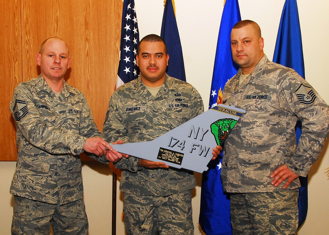 U.S. Air Force Senior Master Sgt. Timothy Campbell and U.S. Air Force Master Sgt. Lyle Sharkey present U.S. Air Force Tech. Sgt Ezekiel Jimenez with a replica tail flash in the 174th Fighter Wing headquarters building at Hancock Field in Syracuse N.Y., on November 6, 2009. Jimenez was presented with the tail flash for training the first group of instructors, at the field training detachment, who will be supporting the upcoming MQ-9 Reaper mission. (U.S. Air Force photo by Tech. Sgt. Jeremy M. Call/Released)