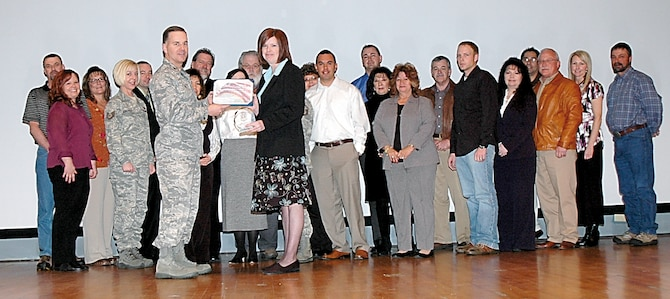 Col. Eric Fox, 748th Supply Chain Management Group commander (left, holding award) presents the Air Force Materiel Command's 2007 Supply Chain management of the Year, Outstanding Supply Chain Management  Team award to the 748th SCMG Shipping and Receiving Wing during a ceremony Jan. 29. Others received awards as well.