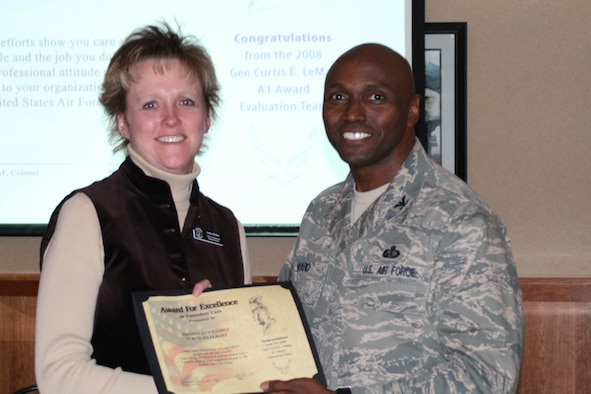 Janice hollen, Airman and Family Readiness Flight chief, accepts an Award for excellence in Customer Care on behalf of her flight from Col. Benjamin Ward, LeMay Team chief, during the LeMay team's departing ceremony Jan. 30 at Hill Air Force Base.