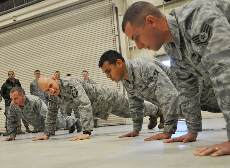 For being late to the 33rd Fighter Wing's propulsion shop, Command Chief Master Sgt. Steve Sullens, Air Combat Command, does pushups with other Airmen handpicked by a squadron member Feb. 5 during the chief's tour of the wing. (U.S. Air Force Photo/Chrissy Cuttita)