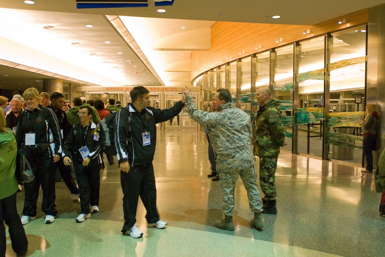 Master Sergeant (MSgt) Neil Ramey, of the 124th Logistics Readiness Squadron, gives a high-five to an athlete from New Zealand who is competing in the 2009 Special Olympics World Winter Games as he arrives in Boise, Idaho. MSgt Ramey is helping with other members of the Joint Task Force (JTF) Special Olympics which has been stood up with members of the Idaho National Guard to provide logistical support for the 2009 Special Olympics World Winter Games. (U.S. Air Force photo by Senior Airman Robert Barney / RELEASED)