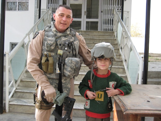 Lt. Col. John Stewart, 519th Combat Sustainment Squadron vice director, takes a photo with Malik during one of the weekly humanitarian missions performed by the coalition. The humanitarian missions provide school supplies, blankets, clothing and food to local villages and schools in their respective area of responsibility.