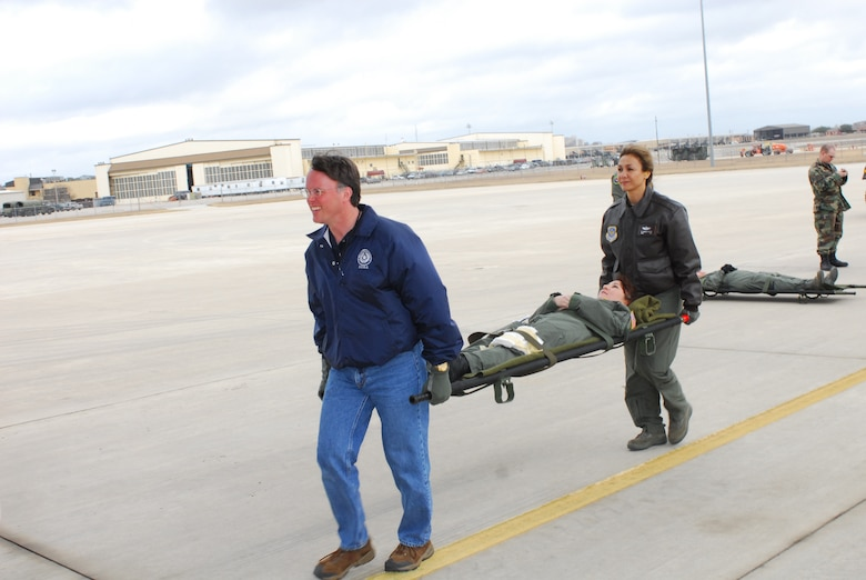 "Dr. David Lakey, commissioner of the Department of State Health Services (DSHS), helps an Airman carry a litter ""patient"" into the back of a C-17 aircraft during a training exercise. He and three other key staff members from the DSHS visited Lackland Air Force Base, Texas, Feb. 7 to learn about the aircraft and its medical evacuation capabilities. (TXMF photo by Tech. Sgt. Rene"