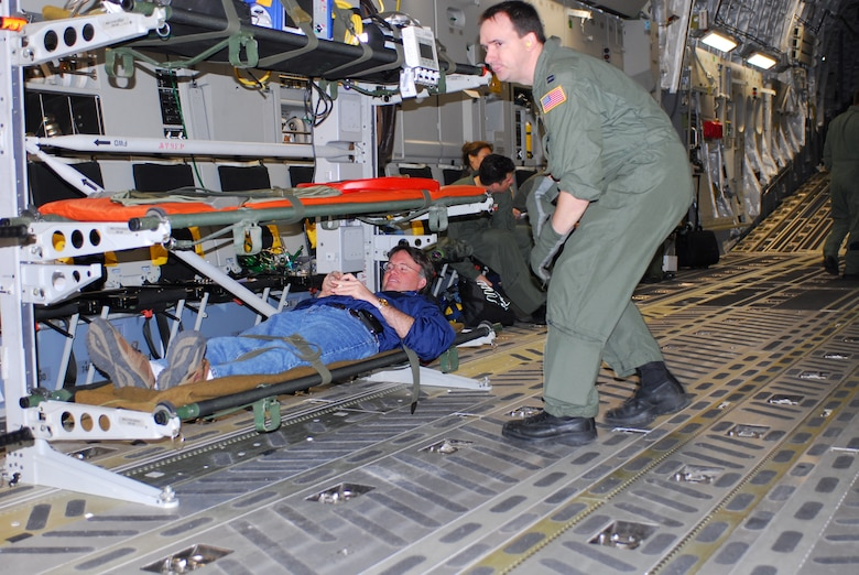Capt. Bill Reed checks on Dr. David Lakey, commissioner of the Department of State Health Services, who takes the role of a litter patient during an exercise aboard a C-17 aircraft Feb. 7. He and three other key staff members from the DSHS board the C-17 at Lackland Air Force Base, Texas, to learn about the aircraft and its medical evacuation capabilities. (TXMF photo by Tech. Sgt. Rene Castillo)