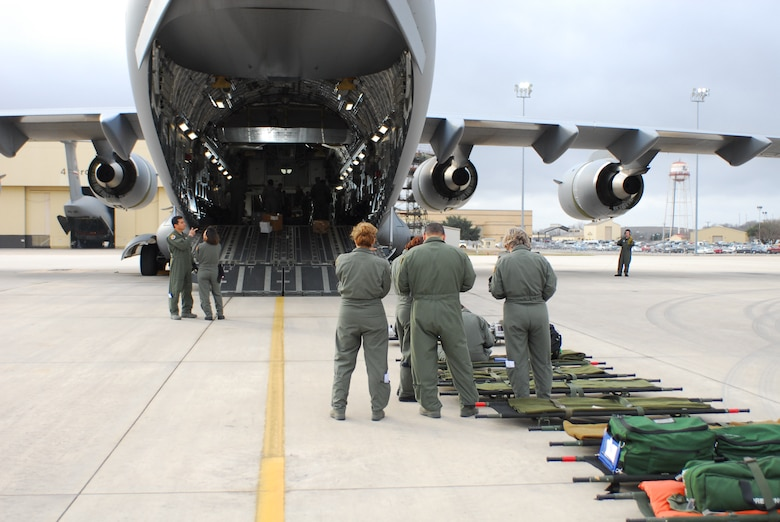 Airmen of the 433rd Aeromedical Evacuation Squadron prepare to load litters in a C-17 aircraft at Lackland Air Force Base Feb. 7 as part of a training exercise. Observing the exercise were four key staff members from the Texas Department of State Health Services. (TXMF photo by Tech. Sgt. Rene Castillo)
