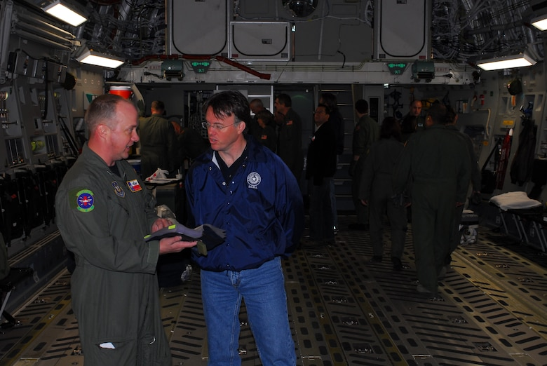 Chief Master Sgt. Rodney Christa, 433rd Aerospace Evacuation Squadron superintendent, explains C-17 aircraft operations to Dr. David Lakey, commissioner of the Department of State Health Services (DSHS), prior to takeoff. Dr. Lakey boarded the C-17 at Lackland Air Force Base, Texas, Feb. 7 to learn about the C-17 and its medical evacuation capabilities. (TXMF photo by Tech. Sgt. Rene Castillo)
