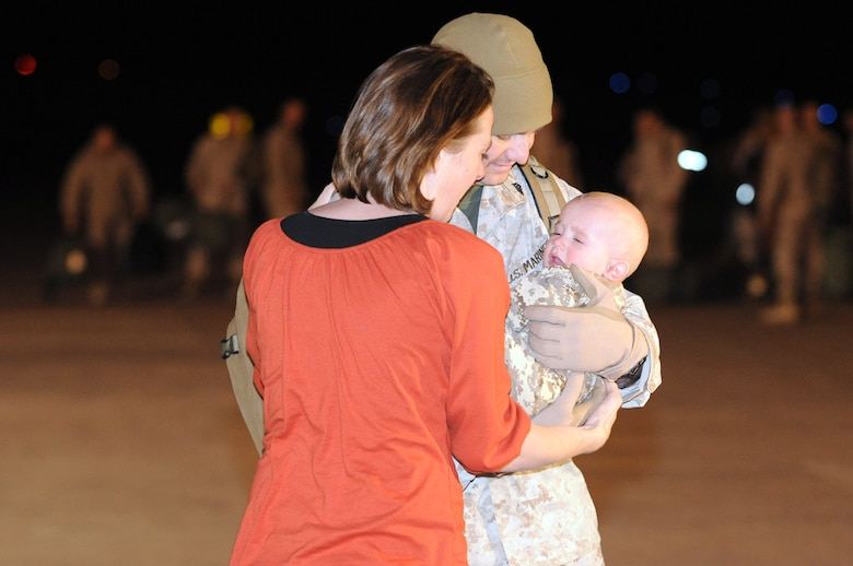BUCKLEY AIR FORCE BASE, Colo. -- Michelle Figler welcomes home her husband Sgt. Josh Figler. This was his first time holding his son Ryder. The Marines returned to Hangar 909 here, Jan. 31, from a seven month deployment to the Anbar Province, Iraq, where they performed tactical air operations. (U.S. Air Force photo by Senior Airman Christopher Bush)