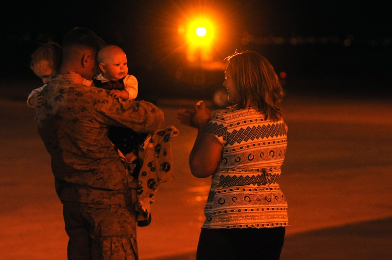 BUCKLEY AIR FORCE BASE, Colo. -- Marine Cpl. Tyler Short returns home to the waiting arms of his children, Mason and Traci, and his wife, Miranda, outside Hangar 909. This was his first time holding his daughter Traci who was born while he was deployed. The Marines returned to Buckley, Jan. 31, from a seven month deployment to the Anbar Province, Iraq, where they performed tactical air operations. (U.S. Air Force photo by Senior Airman Christopher Bush)