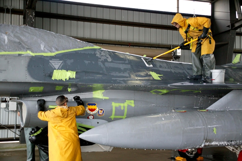 SHAW AIR FORCE BASE, S.C.-- Capt. Scott Hall, 20th Maintenance Operations Squadron and Capt. Joshua Wennrich, 20th Aircraft Maintenance Squadron, scrub down an F-16 in the Wash Rack Feb. 10. Six maintenance group CGOs and four Airmen spent about three hours washing the F-16. The F-16s are washed every 60 days to keep them mission-ready. (U.S. Air Force photo/SSgt Holly Brown)