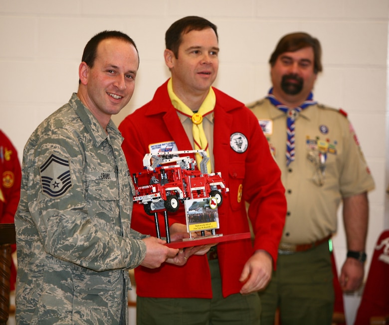 Senior Master Sgt. Robert Zukauskas, information assurance specialist, 103rd Communications Squadron, dressed in his Boy Scout uniform, presents Senior Master Sgt. Robert Cross, Fire Chief, 103rd Civil Engineer Squadron, with a token of appreciation for the Conn. Air National Guard's support of local Boy Scouts while Scott Vujs, Assistant Scout Master, looks on.  (Photo by Rich Tanquay)