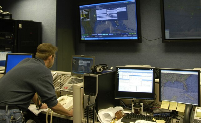Dwight Herndon, an ARINC computer network and systems analyst, sets up a training mission using distributed mission operations technology. Photo by Ms Mary McHale