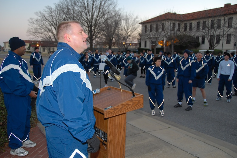"Col. Kris D. Beasley, commander of the 42nd Air Base Wing, greets wing members as they prepare for the Jan. 30 fun run. The run began and ended at the ""prop and wings"" monument in front of building 800. Temperatures were as low as 26 degrees as the runners began their 5K journey through the base. (Air Force photo by Jamie Pitcher)"