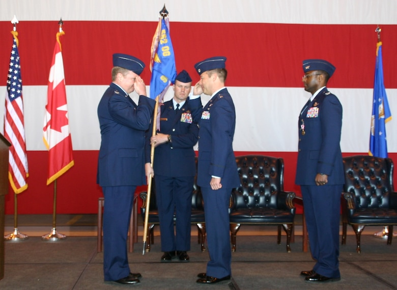 Col. George Carpenter, commander, 552nd Operations Group, salutes Lieutenant Col. Paul Oldham, the new commander of the 960th Airborne Air Control Squadron Vikings, in a ceremony February 12.