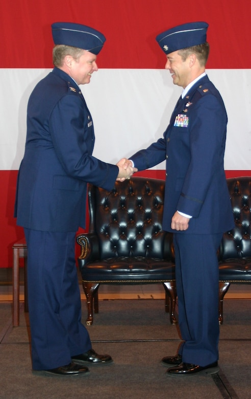 Col. George Carpenter, commander, 552nd Operations Group congratulates the new commander of the 960th Airborne Air Control Squadron Vikings, Lieutenant Col. Paul Oldham, during a change of command ceremony February 12.