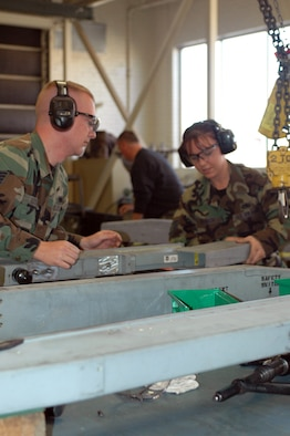 Staff Sgts. Byron Kooima and Kathleen Branch, weapons technicians with the 162nd Armament Flight, remove panels, inspect and perform maintenance on an AIM 9 missile launcher from an F-16. AIM 9s require detailed inspections at a minimum of every 18 months from last service. (Air National Guard photo by Staff Sgt. Desiree Twombly)