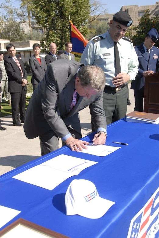 Arizona sports icon Jerry Colangelo, left, signs a Statement of Support for the Employer Support of Guard and Reserve (ESGR) program as Major General Hugo Salazar, The Adjutant General of Arizona, looks on. Other dignitaries present included Phoenix Mayor Phil Gordon, background, far left. (Arizona National Guard photo by Army Sgt. Ed Balaban)