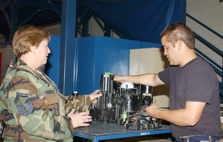 Senior Master Sgt. Yvonne Shealy discusses repairs to an accessory drive gear box that caused suspected aircraft vibration with Staff Sgt. Jaryd Lamore. Sergeant Lamore is an aircraft maintenance technician for the 148th Aircraft Maintenance Flight. (Air National Guard photo by Senior Airman Sarah Elliott)