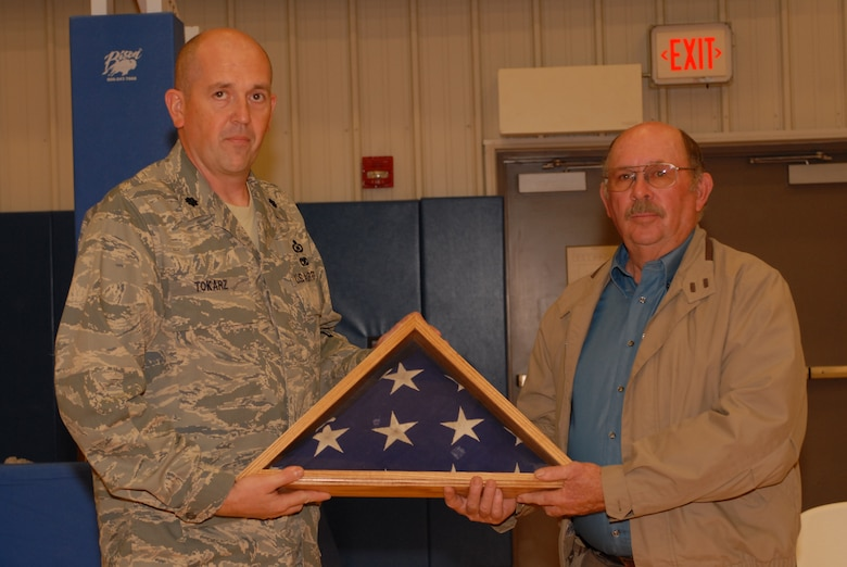 Lt Col Mike Tokarz, 134 ACS Commander, presents the recovered flag to Mr. Gene West, Chariman of the County Commissioners and fifth generation Greensburg resident.