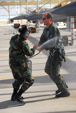 """Lt. Col. Bruce Patch, an F-16 pilot, gets hosed down on the flightline by Staff Sgt. Annie Jaramillo after his fini flight here Feb. 12. When Colonel Patch announced his fini flight to friends and co-workers weeks prior, a flood of volunteers came forward for the honor of drenching him. In turn, he raffled the opportunity among wing members at $1 per ticket to benefit the 162nd Fighter Wing Family Readiness Group. The raffle raised more than $100 to benefit Guard families. """"I was hoping this raffle would become a tradition among pilots who retire from the 162nd. It's for a good cause,"""" said Colonel Patch. He and his wife Tracy will move to Denver, Colo., where he will assume a position as a quality manager with the Veteran's Administration's Health Administration Center heading a Lean process. (Air National Guard photo by Master Sgt. Dave Neve)"""