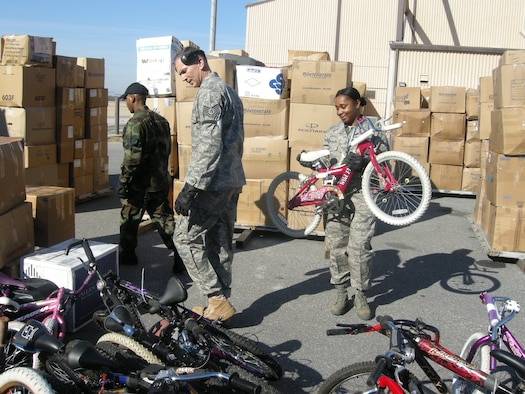 """ANDREWS AIR FORCE BASE, Md. -- (From left) Staff Sgt. Darryl Jordan and Tech. Sgts. Jerry Trickett and Karen Robinson-Hill stack bicycles to load on pallets  Feb. 7. About 20 members of the 69th Aerial Port Squadron loaded more than 16 pallets of school supplies, clothing, toys and tools to be sent to Aschiana School in Kabul, Afghanistan, as part of """"Opportune Airlift."""" Cargo is moved through the Defense Transportation System on a space-available basis by air, surface, sea or a combination thereof for the purpose of ongoing relief and development projects. Sergeant Jordan is a 69th APS air transportation journeyman and Sergeants Trickett and Robinson-Hill are air transportation craftsmen. (U.S. Air Force photo/Tech. Sgt. Amaani Lyle)"""