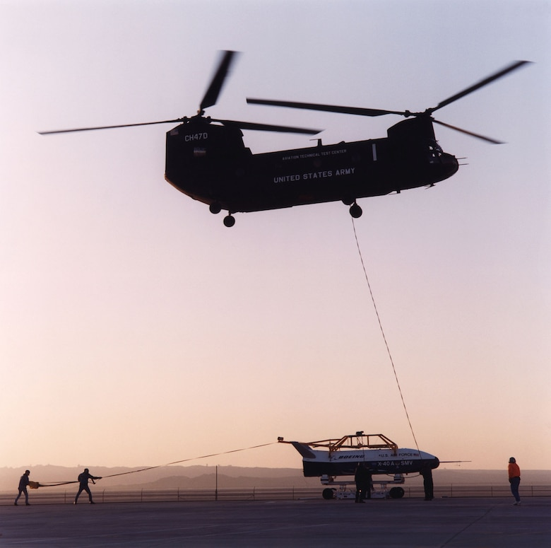 Boeing X-40A being lifted by a CH-47 helicopter for a free-fall test. Note the two support personnel holding the drag parachute behind the aircraft. Used to stabilize the X-40A while being lifted, the parachute was released just before the aircraft was released. (Photo courtesy of NASA)
