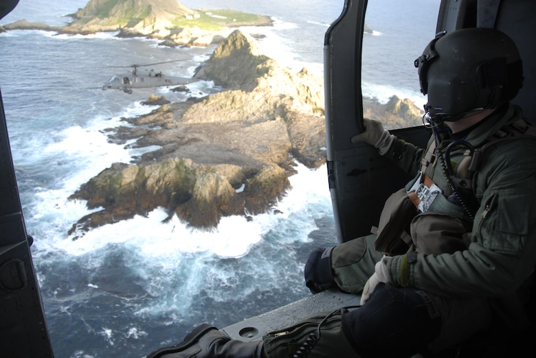 Staff Sgt. Andrew Hedin, an HH-60G Pave Hawk flight engineer from the 129th Rescue Wing at Moffett Federal Airfield, observes another Pave Hawk as it flies over the Farallon Islands.  The unit supported the U.S. Fish and Wildlife Service by helping transport 48 new photovoltaic batteries to power a lighthouse and workshop at the Fish and Wildlife Service research facility in the Farallon National Wildlife Refuge Feb. 17. (U.S. Air Force photo by Tech Sgt. Ray Aquino)(RELEASED)